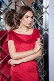 一个美丽的女孩的画象一件红色礼服的在backgroun 免版税库存图片