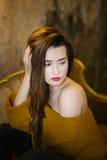 一个美丽的女孩的画象一件黄色毛线衣的 免版税图库摄影
