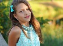 一个美丽的女孩的画象一件蓝色摆在的礼服和的装饰品的户外 免版税库存图片