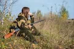 一个美丽的女孩的画象伪装猎人的与猎枪 免版税库存图片