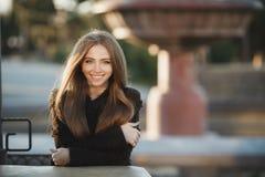 一个美丽的女孩的画象在街道咖啡馆的一张桌上 免版税库存照片