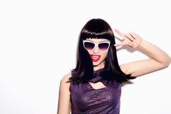 一个美丽的女孩的画象太阳镜和淡紫色衬衣的在背景的演播室 免版税库存照片