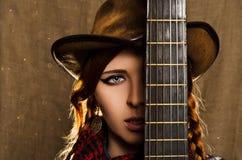 一个美丽的女孩的画象有一把吉他的在乡村模式 库存照片