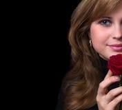 一个美丽的女孩的画象有一朵红色玫瑰的在她的手上 图库摄影