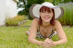 一个美丽的女孩的画象有夏天帽子的,说谎在草 免版税库存图片