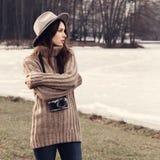 一个美丽的女孩的画象有照相机的在帽子 免版税图库摄影