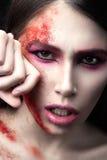 一个美丽的女孩的画象有红色油漆的在她的面孔 艺术秀丽图象 免版税库存图片