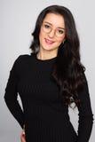 一个美丽的女孩的画象有黑发的在灰色 免版税库存图片
