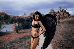 一个美丽的女孩的画象有黑色的飞过邪魔 库存图片