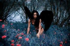 一个美丽的女孩的画象有黑色的飞过邪魔 库存照片