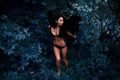 一个美丽的女孩的画象有黑色的飞过邪魔 免版税库存照片