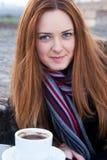 一个美丽的女孩的画象用红色头发饮用的咖啡 免版税库存图片