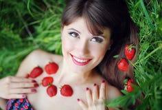 一个美丽的女孩的画象用草莓在公园 库存照片