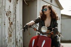 一个美丽的女孩的画象皮夹克的,胸罩和玻璃临近红色摩托车 库存图片