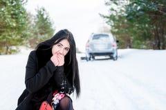 一个美丽的女孩的画象,汽车在发生故障 免版税库存图片
