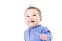 一个美丽的女婴的画象有卷发的在一件蓝色毛线衣 免版税库存图片