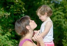 一个美丽的妈妈是拥抱给她的女儿 免版税库存照片