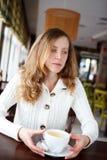 一个美丽的孤独的哀伤的女孩的画象有一杯茶的在咖啡馆的 库存照片