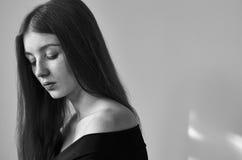 一个美丽的孤独的女孩的剧烈的黑白画象有雀斑的在演播室射击的白色背景 库存照片