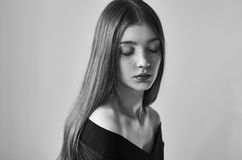 一个美丽的孤独的女孩的剧烈的黑白画象有雀斑的在演播室射击的白色背景 库存图片