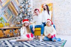 一个美丽的家庭的圣诞节照片有两个孩子的在圣诞老人红色盖帽和红色礼物 坐 免版税图库摄影