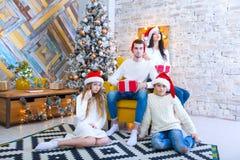 一个美丽的家庭的圣诞节照片有两个孩子的在圣诞老人红色盖帽和红色礼物 坐 免版税库存图片