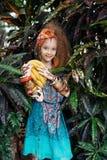 一个美丽的小女孩用穿在密林或雨林的香蕉当地服装 图库摄影