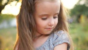 一个美丽的小女孩的一张美丽的接近的画象有长的头发和灰色眼睛的 婴孩改正头发并且降下下来 股票录像