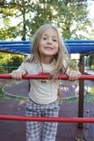 一个美丽的小女孩的画象在操场 免版税库存图片