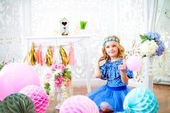 一个美丽的小女孩的画象在演播室装饰了许多颜色气球 图库摄影