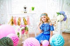 一个美丽的小女孩的画象在演播室装饰了许多颜色气球 免版税库存图片