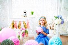 一个美丽的小女孩的画象在演播室装饰了许多颜色气球 库存图片