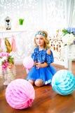 一个美丽的小女孩的画象在演播室装饰了许多颜色气球 库存照片