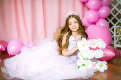一个美丽的小女孩的画象在演播室装饰了许多颜色气球 免版税库存照片