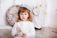 一个美丽的小女孩的画象一件白色礼服和冠的 免版税库存照片