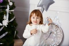一个美丽的小女孩的画象一件白色礼服的在inte 库存照片