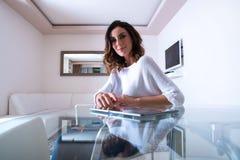 一个美丽的少妇在桌上 免版税库存照片