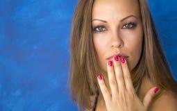 一个美丽的少妇在嘴附近握一只手 画象 免版税库存照片