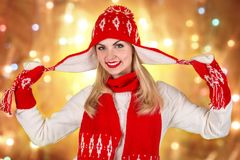 一个美丽的少妇的画象一个被编织的红色帽子、围巾和手套的有圣诞节装饰品的 库存图片
