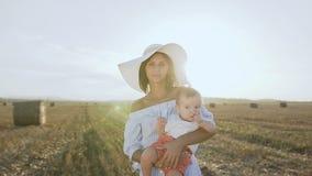 一个美丽的少妇的画象一件礼服的有一个大帽子和她的小儿子的站立在金黄的一个白色身体的 股票视频