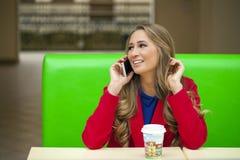 一个美丽的少妇的画象叫由电话 免版税库存照片