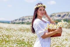 一个美丽的少妇的画象春黄菊领域的 收集雏菊的愉快的女孩 休息在春黄菊的领域的女孩 S 免版税库存图片