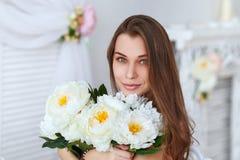 一个美丽的少妇的画象有一束花的 免版税库存照片