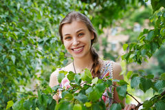 一个美丽的少妇的画象绿色叶子背景的  免版税库存照片