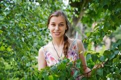 一个美丽的少妇的画象绿色叶子背景的  库存图片
