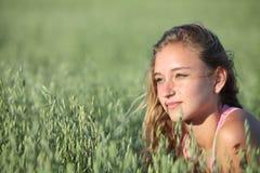 一个美丽的少年女孩的画象在燕麦草甸 免版税库存照片