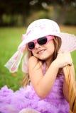 一个美丽的帽子和太阳镜的小女孩在一个夏天p 免版税库存照片