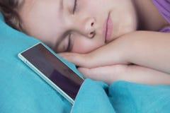 一个美丽的平静的女孩在床上睡觉,在她的电话旁边,警报很快将敲响 免版税库存照片