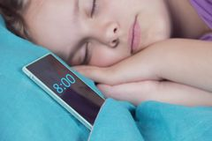 一个美丽的平静的女孩在床上睡觉,在她的电话旁边,警报很快将敲响 免版税库存图片