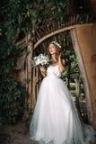 一个美丽的年轻性感的女孩新娘的画象有花的在她的头发看起来有吸引力在夏天背景的一件白色礼服  免版税图库摄影